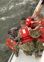 In this photo provided by the U.S. Coast Guard, crew members of the Coast Guard Cutter Glenn Harris pull a person from the water Tuesday, April 13, 2021 after a 175-foot commercial lift boat capsized 8 miles south of Grand Isle, La. The Seacor Power, an oil industry vessel, flipped over Tuesday in a microburst of dangerous wind and high seas. (U.S. Coast Guard via AP)