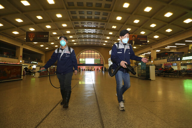 Workers spray disinfectant at a train station in Wuhan in southern China's Hubei province, Wednesday, Jan. 22, 2020. Chinese health authorities urged people in the city of Wuhan to avoid crowds and public gatherings, after warning on Wednesday that a new viral illness that has infected hundreds and caused at least nine deaths could spread further. (Chinatopix via AP)