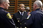 United States Surgeon General Jerome Adams, center, speaks with Arlington, Mass., Police Chief Frederick Ryan, left, and a Boston police law enforcement officer, during a break at a national summit focused on police efforts to address the opioid epidemic, Thursday, Dec. 6, 2018, in Boston. (AP Photo/Steven Senne)