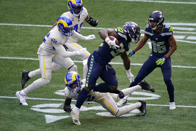 Seattle Seahawks running back Chris Carson (32) rushes against the Los Angeles Rams during the first half of an NFL football game, Sunday, Dec. 27, 2020, in Seattle. (AP Photo/Elaine Thompson)