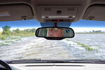 In this June 27, 2019 photo, Gene Walter, of Crescent, Iowa, drives his truck through a flooded road that sits between flooded fields in Crescent, Iowa. This year's record rainfall and devastating flooding are forcing tough decisions about the future of farming in in the face of climate change. Like many in the water-weary Midwest, Walter doesn't know if climate change was responsible for the second major flood in nine years. Or the increasingly frequent torrential rains that dump more water in an hour than he used to see in days. (AP Photo/Nati Harnik)