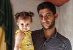 """In this Sunday September 1, 2019 photo, Abdel Hamid al-Yousef poses for a picture with his 11-month-old daughter Aya, at a displaced settlement near the Turkish border called """"Mokhayyam al-Karamah,"""" Arabic for """"Dignity Camp,"""" near the town of Atmeh, in northern Syria. Al-Yousef lost his baby twins, his wife and 16 other relatives in the poison gas attack that hit Syria's Khan Sheikhoun in April 2017. Determined to continue with his life, he remarried, and has an 11-month-old daughter. But tragedy keeps chasing the 31-year-old former shopkeeper as he recently fled a government assault on Idlib and the nonstop bombardment of Khan Sheikhoun. (AP Photo)"""