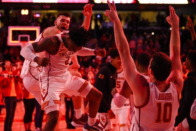 Southern California guard Jonah Mathews, center, celebrates with Nick Rakocevic, back, after USC defeated Stanford 82-78 in overtime of an NCAA college basketball game, as Quinton Adlesh, right, watches in Los Angeles, Saturday, Jan. 18, 2020. (AP Photo/Kelvin Kuo)