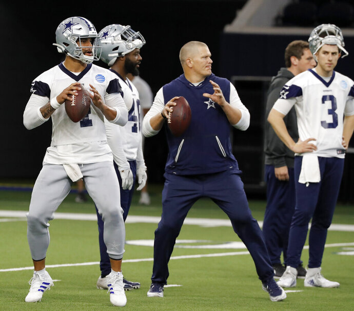 Dallas Cowboys quarterback Dak Prescott (4) and quarterbacks coach Jon Kitna, center, prepare to throw passes as quarterback Mike White (3) looks on during drills at the team's NFL football training facility in Frisco, Texas, Wednesday, June 12, 2019. (AP Photo/Tony Gutierrez