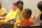 Brian Steven Smith wearing an orange shirt sits with unidentified suspects in a courtroom in Anchorage, Alaska Monday, Oct. 21, 2019. Smith entered an innocent plea Monday in an Anchorage courtroom. He earlier pleaded not guilty in the death of 30-year-old Kathleen Henry, a homeless Alaska Native woman. During his interrogation, police say he confessed to killing another Alaska Native woman. Police won't say if there may be other victims. (AP Photo/Mark Thiessen)