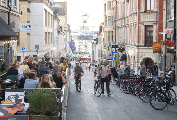 People with bicycles pass an outdoor restaurant on a street in the Sodermalm neighbourhood of Stockholm, Thursday, August 20, 2020. (Fredrik Sandberg/TT News Agency via AP)