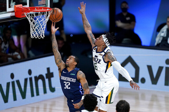 Dallas Mavericks Trey Burke (32) shoots under Utah Jazz's Rayjon Tucker (6) during the second half of an NBA basketball game Monday, Aug. 10, 2020, in Lake Buena Vista, Fla. (AP Photo/Ashley Landis, Pool)