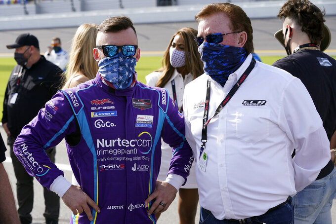 Austin Dillon, left, talks with his grandfather Richard Childress on pit road before the start of the Rolex 24 hour auto race at Daytona International Speedway, Saturday, Jan. 30, 2021, in Daytona Beach, Fla. (AP Photo/John Raoux)