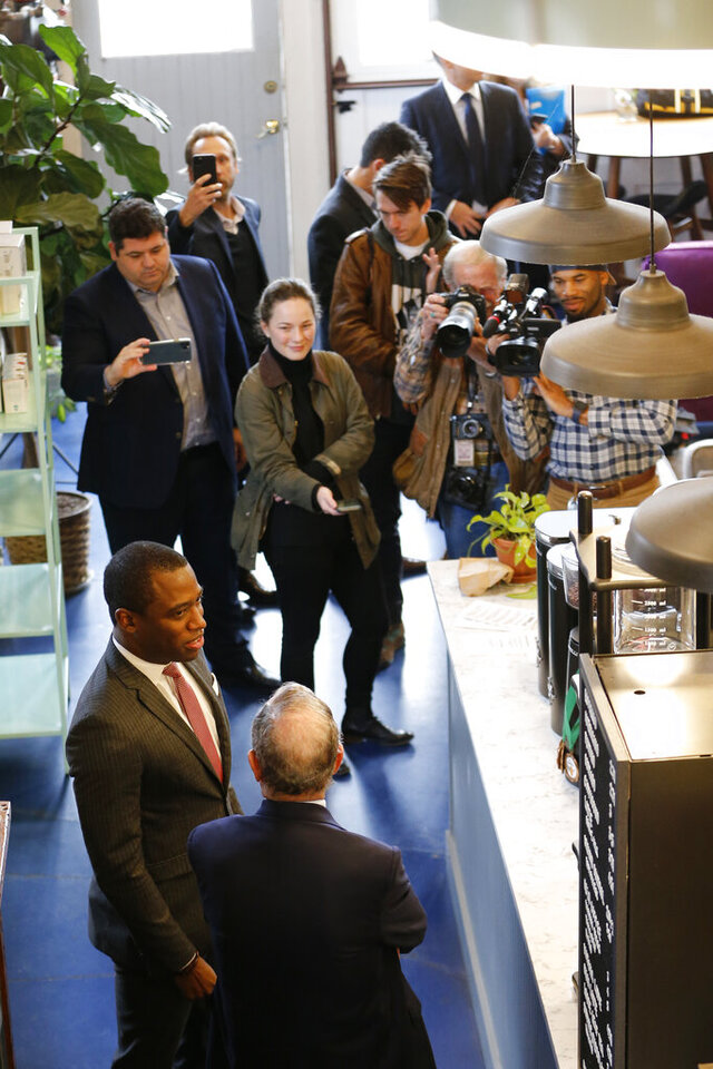 Democratic presidential candidate, former New York Mayor Michael Bloomberg, front back to camera, chats with Richmond mayor Levar Stoney, front left, under the watchful eye of the media at a coffee shop in Richmond, Va., Tuesday, Jan. 7, 2020. (AP Photo/Steve Helber)