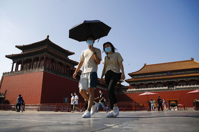Visitors wearing face masks to help protect against the coronavirus visit Forbidden City in Beijing, Thursday, Aug. 13, 2020. New local cases in China fell into the single digits, while Hong Kong saw another rise in hospitalizations and deaths. (AP Photo/Andy Wong)