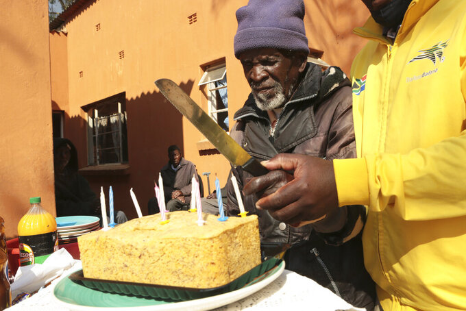 A 103 year old man is helped to cut a banana bread cake during his birthday celebrations at Melfort Old People's home on the outskirts of Harare, Zimbabwe, Sunday, July 25, 2021. The economic ravages of COVID-19 are forcing some families in Zimbabwe to abandon the age old tradition of taking care of the elderly. Zimbabwe's care homes have experienced a 60% increase in admissions since the outbreak of the pandemic in March last year. (AP Photo/Tsvangirayi Mukwazhi)