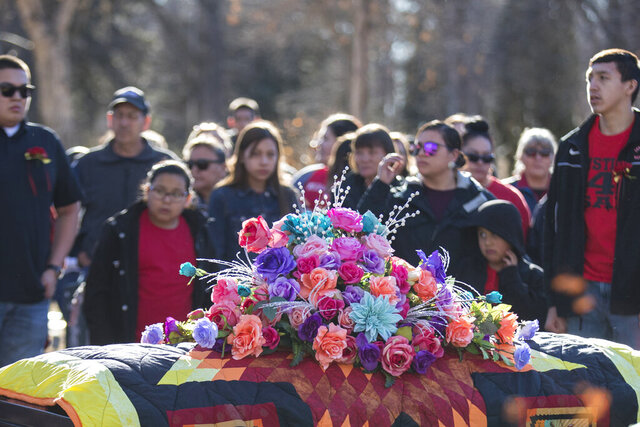 Flowers rest on top of Selena Not Afraid's casket during her funeral at the Fairview Cemetery in Hardin, Mont. on Sunday, Jan. 26, 2020. More than 1,000 people attended the funeral for the 16-year-old Hardin girl who died of hypothermia after reportedly walking away from an Interstate 90 rest stop on New Year's Day.  The circumstances leading to Selena's death are still being investigated.  (Mike Clark/The Billings Gazette via AP)