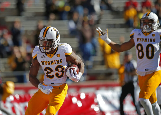Wyoming running back Xazavian Valladay (23) scores a touchdown against New Mexico during the first half of an NCAA college football game in Albuquerque, N.M., Saturday, Nov. 24, 2018. (AP Photo/Andres Leighton)