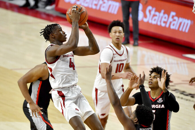 Arkansas guard Davonte Davis (4) shoots the ball over Georgia defenders during the second half of an NCAA college basketball game Saturday, Jan. 9, 2021, in Fayetteville, Ark. (AP Photo/Michael Woods)
