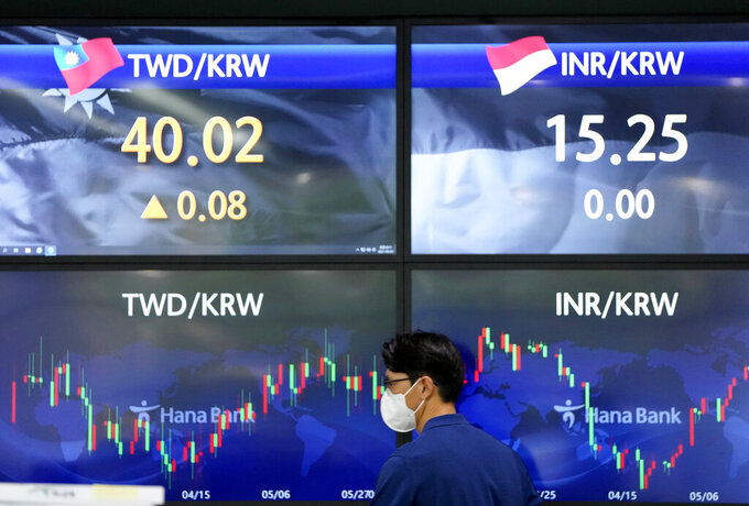 A currency trader walks near the screens showing the foreign exchange rates at the foreign exchange dealing room in Seoul, South Korea, Thursday, June 3, 2021. Shares have advanced in Asia Thursday after a day of modest gains on Wall Street led by buying of energy and technology stocks. Oil prices also rose. (AP Photo/Lee Jin-man)