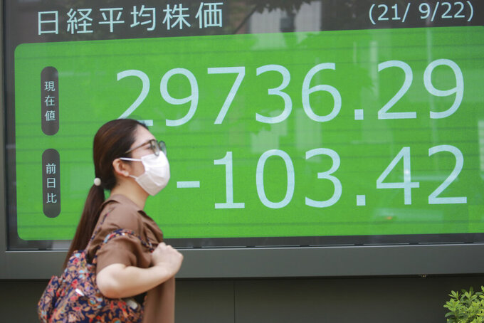 A woman walks by an electronic stock board of a securities firm in Tokyo, Wednesday, Sept. 22, 2021. Asian shares were mostly lower on Wednesday after major indexes ended mixed on Wall Street.(AP Photo/Koji Sasahara)