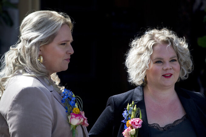 Jeanette, left, and Romy Van Nus answer questions during an interview after their wedding ceremony in Utrecht, Netherlands, Thursday, April 1, 2021. Twenty years ago, on April 1, 2001, the mayor of Amsterdam married four couples in City Hall as the Netherlands became the first country in the world with legalized same-sex marriage. It's now legal in 28 countries. (AP Photo/Peter Dejong)