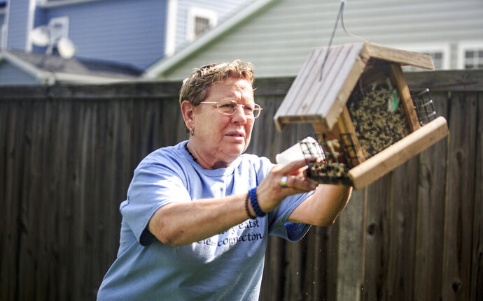In this July 10, 2019 photo, 61-year-old Army veteran Joyce Leteiller fills up a bird feeder with seed in her sister's home in Hanahan, S.C. Leteiller has struggled with PTSD, depression, drug and alcohol addiction and suicide in the past, but has since found bird watching and reading to be essential in her path to healing. (Sylvia Jarrus/The Post And Courier via AP)