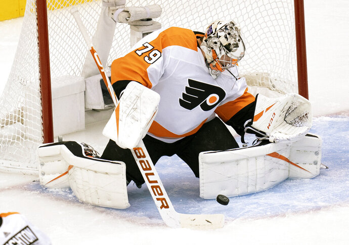Philadelphia Flyers goaltender Carter Hart (79) makes a save against the Boston Bruins during first-period NHL hockey playoff action in Toronto, Sunday, Aug. 2, 2020. (Frank Gunn/The Canadian Press via AP)