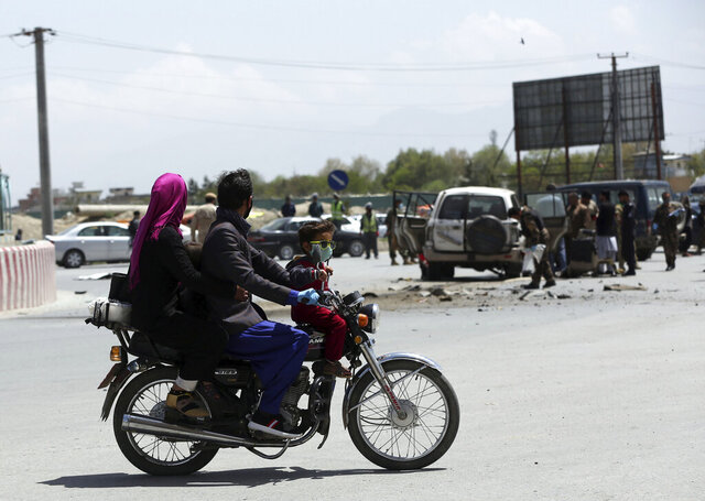 A man rides his motorbike near the site of a bomb explosion in Kabul, Afghanistan, Monday, April 27, 2020. Kabul police said a sticky bomb attached to a vehicle detonated in the capital but caused no casualties. (AP Photo/Rahmat Gul)