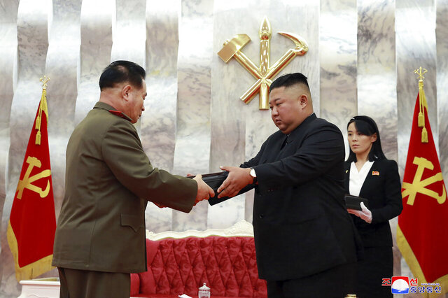 "In this Sunday, July 26, 2020, photo released by the North Korean government, North Korean leader Kim Jong Un, center, hands over a ""Paektusan"" commemorative pistol to a senior military official during a ceremony in Pyongyang, North Korea. At right is Kim's powerful sister Kim Yo Jong. Independent journalists were not given access to cover the event depicted in this image distributed by the North Korean government. The content of this image is as provided and cannot be independently verified. Korean language watermark on image as provided by source reads:"