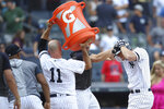 Teammates prepare to douse New York Yankees' DJ LeMahieu, right, after he hit the gam- winning walk off home run in the 11th inning of a baseball game against the Oakland Athletics, Saturday, Aug. 31, 2019, in New York. (AP Photo/Mary Altaffer)