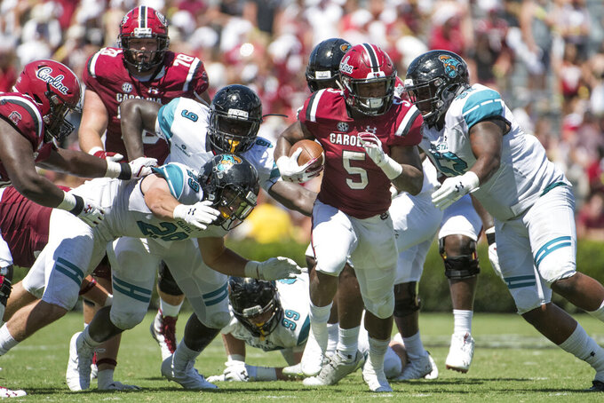 FILE - In this Sept. 1, 2018, file photo, South Carolina running back Rico Dowdle (5) carries the ball against Coastal Carolina's Silas Kelly (29), Tarron Jackson (9), and C.J. Brewer (52) during the second half of an NCAA college football game in Columbia, S.C. Jackson led the Sun Belt in sacks last year with 10 and returns for his senior season as a contender to be the conference defensive player of the year. (AP Photo/Sean Rayford, File)