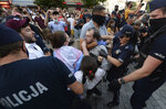 Police scuffle with pro-LGBT protesters angry at the arrest of an LGBT activist in Warsaw Poland on Friday, Aug. 7, 2020.The incident comes amid rising tensions in Poland between LGBT activists and a conservative government that is opposed to LGBT rights.(AP Photo/Czarek Sokolowski)