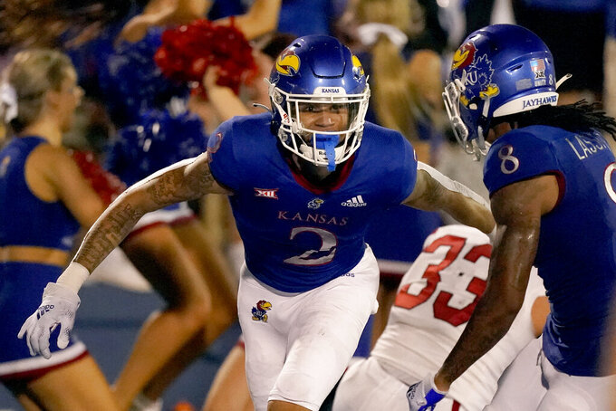 Kansas wide receiver Lawrence Arnold (2) celebrates with wide receiver Kwamie Lassiter II (8) after scoring a touchdown during the second half of an NCAA college football game against South Dakota Friday, Sept. 3, 2021, in Lawrence, Kan. Kansas won 17-14. (AP Photo/Charlie Riedel)