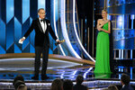 This image released by NBC shows Tom Hanks accepting the Cecil B. DeMille Award as presenter Charlize Theron looks on at right at the 77th Annual Golden Globe Awards at the Beverly Hilton Hotel in Beverly Hills, Calif., on Sunday, Jan. 5, 2020. (Paul Drinkwater/NBC via AP)