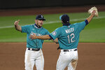 Seattle Mariners' Kyle Seager, left, and Evan White (12) keep their distance as they celebrate after the team beat the Oakland Athletics in a baseball game during the Mariners home opener Friday, July 31, 2020, in Seattle. The Mariners won 5-3.(AP Photo/Elaine Thompson)