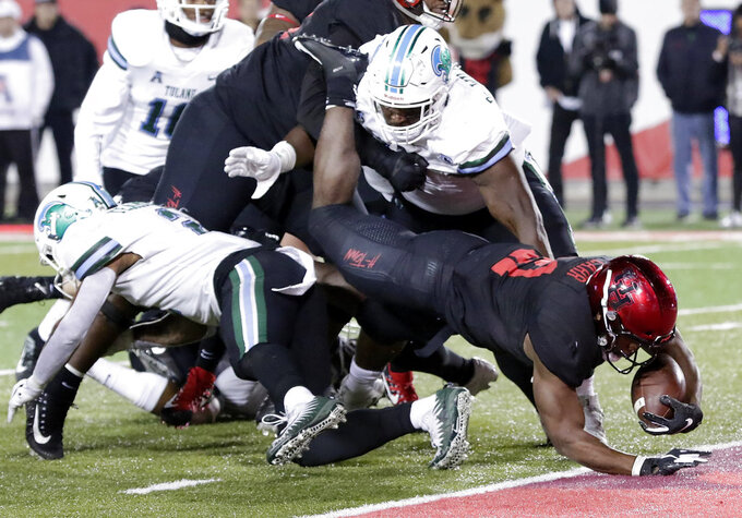 Houston running back Patrick Carr (21) dives between Tulane safety Roderic Teamer Jr., left, and nose tackle De'Andre Williams, right, during the first half of an NCAA college football game Thursday, Nov. 15, 2018, in Houston. (Michael Wyke/Houston Chronicle via AP)