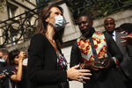 Belgium's Prime Minister Sophie Wilmes speaks with the public after unveiling a plaque during celebrations marking the 60th anniversary of Congo's independence from Belgium in the Brussels district of Matonge, Tuesday, June 30, 2020. (Francisco Seco)