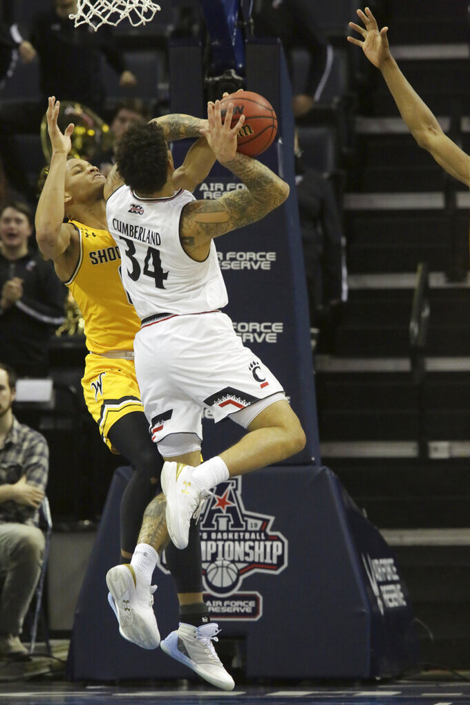 Wichita State's Logan Johnson blocks a layup attempt by Cincinnati's Jarron Cumberland in the second half of an NCAA college basketball game at the American Athletic Conference tournament Saturday, March 16, 2019, in Memphis, Tenn. (AP Photo/Troy Glasgow)