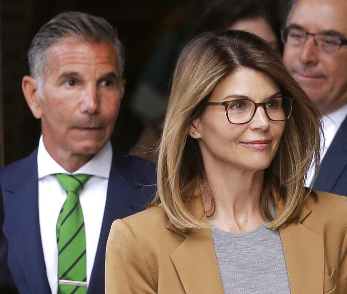 FILE - In this April 3, 2019 file photo, actress Lori Loughlin, front, and husband, clothing designer Mossimo Giannulli, left, depart federal court in Boston after facing charges in a nationwide college admissions bribery scandal. Loughlin and her husband Giannulli said in court documents Monday, April 15, 2019, that they are pleading not guilty to charges that they took part in a sweeping college admissions bribery scam.  (AP Photo/Steven Senne, File)