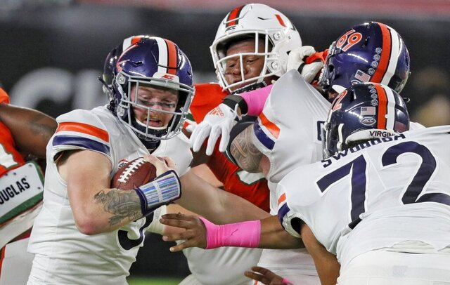 The Miami defense pressures Virginia quarterback Brennan Armstrong (5) on a keeper in the first quarter of an NCAA college football game in Miami Gardens, Fla., Saturday, Oct. 24, 2020. (Al Diaz/Miami Herald via AP)
