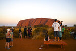 In this Oct. 10, 2019, photo, tourists view the sandstone monolith called Uluru that dominates Australia's arid center at Uluru-Kata Tjuta National Park. Oct. 25, 2019 will see the end of visitors enjoying the panoramic views of the incongruously flat Outback surrounds from the rock's summit also marks indigenous Australians finding a new voice in national decision-making. (Lukas Coch/AAP Image via AP)