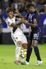 LA Galaxy midfielder Jonathan dos Santos, left, collides with Montreal Impact forward Orji Okwonkwo during the first half of an MLS soccer match in Carson, Calif., Saturday, Sept. 21, 2019. (AP Photo/Chris Carlson)