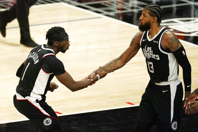 Los Angeles Clippers guard Reggie Jackson, left, congratulates guard Paul George after George scored during the second half of an NBA basketball game against the Minnesota Timberwolves Sunday, April 18, 2021, in Los Angeles. (AP Photo/Mark J. Terrill)