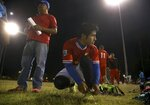 Pedro Chilel, 21, abandoned by his parents in Guatemala before he traveled alone to the United States at age 17, ties his shoes before his Maya Chapin soccer league game Wednesday, April 17, 2019, in Phoenix. As is common in Guatemalan indigenous communities ravaged by alcoholism, Chilel was abandoned by his parents before traveling to the U.S. alone at 17. He now lives in Phoenix, where he has permanent U.S. residency, a landscaping job and a sense of community he lacked in his village of Mirador.  Antonio Velasquez, pastor and director of the soccer league, stands behind Chilel. (AP Photo/Ross D. Franklin)
