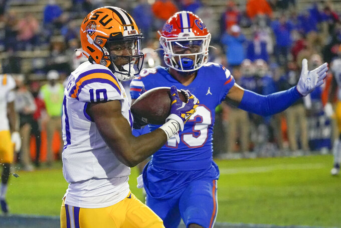 LSU wide receiver Jaray Jenkins, left, catches a 5-yard pass for a touchdown in front of Florida defensive back Donovan Stiner during the first half of an NCAA college football game Saturday, Dec. 12, 2020, in Gainesville, Fla. (AP Photo/John Raoux)
