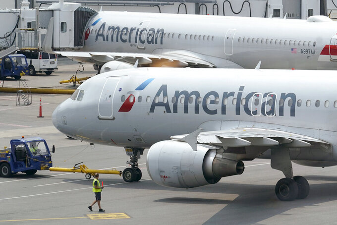 American Airlines passenger jets prepare for departure, Wednesday, July 21, 2021, near a terminal at Boston Logan International Airport, in Boston. American Airlines is planning to invest in a small South American budget airline as part of a deal that will include selling seats on each other's flights. American announced the proposed deal with JetSmart on Thursday, July 29. (AP Photo/Steven Senne)