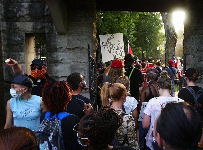 A protester directs the crowd to stop filing through a pedestrian gate leading to Portland Place after the first group who walked through encountered a couple pointing guns at the them enroute to St. Louis Mayor Lyda Krewson's house Sunday, June 28, 2020, in the Central West End of St. Louis. The protesters called for Krewson's resignation for releasing the names and addresses of residents who suggested defunding the police department. (Laurie Skrivan/St. Louis Post-Dispatch via AP)