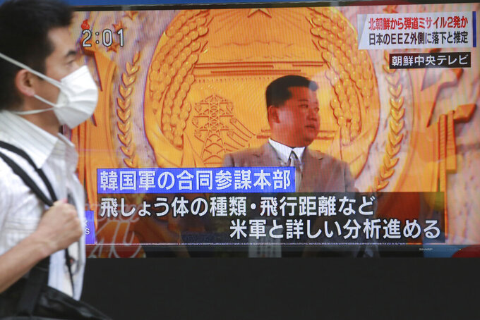 """A man walks past a TV screen showing North Korean leader Kim Jong Un, in Tokyo, Wednesday, Sept. 15, 2021. North Korea fired two ballistic missiles into waters off its eastern coast Wednesday afternoon, two days after claiming to have tested a newly developed missile in a resumption of its weapons displays after a six-month lull. Letters, bottom, read """"Will analyze details with U.S. military forces on projectile, flight distance and so on."""" (AP Photo/Koji Sasahara)"""