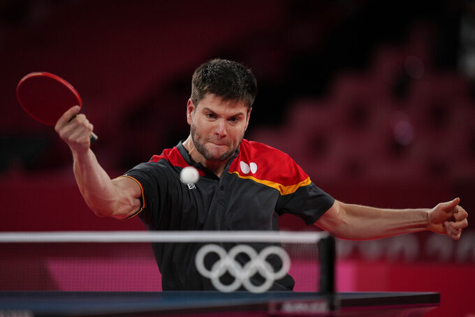 Germany's Dimitrij Ovtcharov returns the ball against China's Ma Long during the table tennis men's singles semifinal at the 2020 Summer Olympics, Thursday, July 29, 2021, in Tokyo. (AP Photo/Kin Cheung)