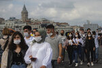 Backdropped by Istanbul's iconic Galata Tower, people wearing masks for protection against the spread of coronavirus, walk over Eminonu bridge in Istanbul, Friday, Sept. 11, 2020. Turkey is getting tough on people who flout self-isolation rules despite testing positive for the coronavirus. An Interior Ministry circular sent to the country's 81 provinces on Friday said people caught leaving their homes despite isolation orders will be quarantined and supervised at state-owned dormitories or hostels. (AP Photo/Yasin Akgul)