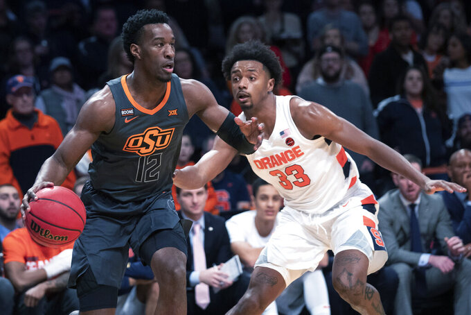 Oklahoma State forward Cameron McGriff (12) drives against Syracuse forward Elijah Hughes (33) during the first half of an NCAA college semi final basketball game in the NIT Season Tip-Off tournament, Wednesday, Nov. 27, 2019, in New York. (AP Photo/Mary Altaffer)