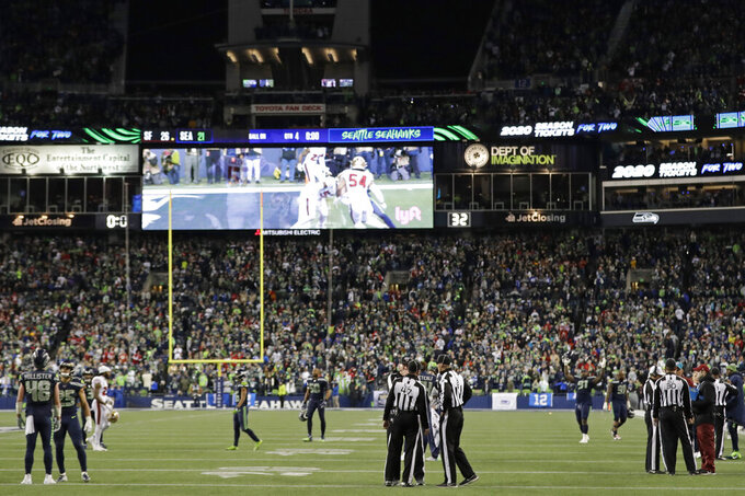 Officials stand on the field as a play involving Seattle Seahawks tight end Jacob Hollister (48) is reviewed late in the second half of an NFL football game against the San Francisco 49ers, Sunday, Dec. 29, 2019, in Seattle. Hollister was ruled down just inches away from the goal line on a fourth-and-goal play and the decision was upheld by the review. The 49ers won 26-21. (AP Photo/Ted S. Warren)