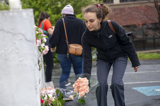 A woman places flowers near a makeshift memorial outside of the Gold Spa in Atlanta, Wednesday, March 17, 2021. Police in the Atlanta suburb of Gwinnett County say they've begun extra patrols in and around Asian businesses there following the shooting at three massage parlors in the area that killed eight, most of them women of Asian descent. (Alyssa Pointer/Atlanta Journal-Constitution via AP)