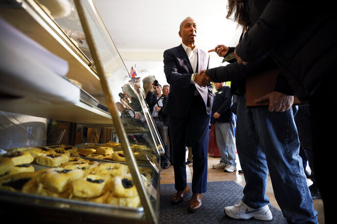 Democratic presidential candidate former Massachusetts Gov. Deval Patrick talks to local residents after placing his order at the Sykora Bakery, Monday, Nov. 18, 2019, in Cedar Rapids, Iowa. (AP Photo/Charlie Neibergall)